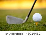 club and white golf ball over grass outdoors - stock photo