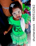 Small photo of Victoria Point, Myanmar- August 8, 2012 : Myanmar girl in green suit. Powder on her face with tradition cal Thanaka Powder.