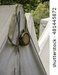 Small photo of Wooden canteen hung by its strap over the top of a canvas tent in a military camp at a reenactment of the American Revolutionary War