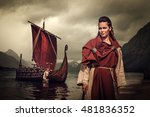 Small photo of Confident viking woman with sword and shield standing near Drakkar on the seashore.