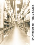Small photo of Blurred image large furniture warehouse with row of aisles and bins from floor to ceiling. Defocused background industrial storehouse interior aisle. Inventory, logistic, export concept.Vintage filter