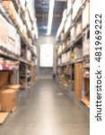 Small photo of Blurred image of large furniture warehouse with row of aisles and bins from floor to ceiling. Defocused background industrial storehouse interior aisle. Inventory, wholesale, logistic, export concept.