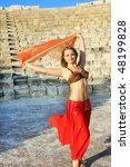Beautiful belly  dancer on the ancient stairs of  Kurion amphitheatre in Cyprus. - stock photo