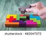 Stock photo hand holding wooden puzzle element hand sets the last element of the puzzle the concept of 482047372