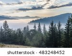 Stock photo fog over mountain range in sunrise light morning sun rays through the fog over mountain slopes 483248452