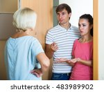 Small photo of Upset mature woman and couple of angry neighbours at doorway
