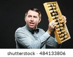Small photo of Aggravated businessman holding an old fashioned abacus on black background