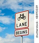 Bicycle lane sing against cloudy sky - stock photo