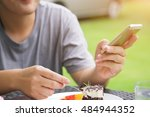 a man eating a cake and playing ... | Shutterstock . vector #484944352