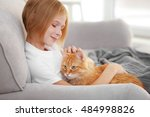 Stock photo cute little girl with red fluffy cat on sofa in room 484998826