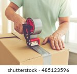 Small photo of Cropped image of handsome mature man in casual clothes packing his stuff into the boxes using an adhesive tape while moving to the new apartment