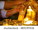 waiter pours beer from the tap | Shutterstock . vector #485195536