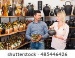 Small photo of Cheerful couple at ceramic store do kitchen-ware shoping