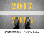 Small photo of Black shoes standing at the line between last year 2016 and new year 2017