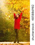 Small photo of Happiness carefree. woman relaxing in autumn park throwing leaves up in the air with arms raised up. Beautiful girl in colorful forest foliage outdoor.