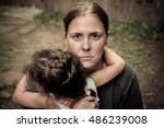 A Woman Holds A Child  Trying...