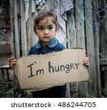 Stock photo little girl holding a sheet of cardboard on the cardboard label i am hungry the child is three 486244705