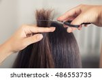 Small photo of Hairdresser trimming brown hair with scissors. Haircut closeup. Getting rid of those split ends