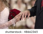 happy bride puts the ring on the groom's finger - stock photo