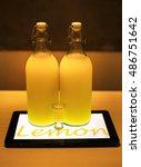 Small photo of Lemoncello cocktail in two big bottles and small shot glass on table lighted by tablet underneath in cafe, ambient light photo