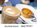 A frothy latte coffee, with a passionfruit tart in the background. - stock photo