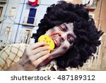 Small photo of closeup of a scary zombie with an afro hairdo eating a pumpkin-shaped cookie