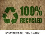 Small photo of Recycling symbol and one hundred per cent recycled sign on the side of a hessian bag in green
