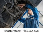 Low angle view of male mechanic repairing suspension system of car in garage - stock photo