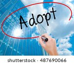 Small photo of Man Hand writing Adopt with black marker on visual screen. Business, technology, internet concept. Modern business skyscrapers background. Stock Photo