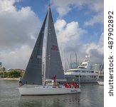 Small photo of Honolulu, Hawaii, USA, Sept. 23, 2016: Swift racing boat and crew sailing out of the Ala Wai Harbor with Ala Moana Shopping Center in the background.
