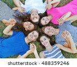 happy friends lying on grass | Shutterstock . vector #488359246