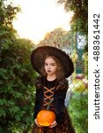 Small photo of Eve of All Saints' Day. Beautiful little girl portrays the evil fairy. She is wearing a dark dress and a hat. On her face make-up. In the hands of the girl Jack-o-lantern.Children adore Halloween.
