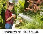 Beautiful young woman watering garden