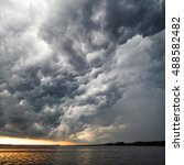 Small photo of Amazing view of gorgeous thunderstorm clouds above water