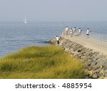 People fishing on a hazy afternoon in Laurence Harbor along the New Jersey shore. - stock photo