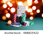Small photo of Casino chips and cards, two aces on the playing green table against bright bokeh lights background. Poker game theme backdrop