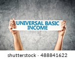 Small photo of Universal basic income concept with hands holding banner