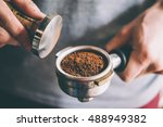 Barista presses ground coffee using tamper. Toned picture - stock photo