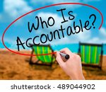 Small photo of Man Hand writing Who Is Accountable? with black marker on visual screen. Isolated on sunbed on the beach. Business, technology, internet concept. Stock Image