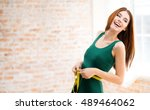 young happy woman measuring her ... | Shutterstock . vector #489464062
