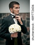 Small photo of Attractive groom with whiskers adjusts his bow tie while holding wedding bouquet in another hand