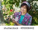 Stock photo happy mature woman is cutting rose in garden 490008442