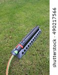 Small photo of Modern oscillating sprinkler on the mown lawn in the summer garden