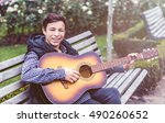 Young man while sitting on the bench playing on acoustic guitar outdoor