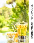 Small photo of Concept of herbal tea with honey and accessories. Camomile tea in a glass mug. Green meadow background with trees. Light airy capture. Vertical