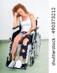 Small photo of Dejected disabled young woman in a wheelchair with her leg in a brace following knee surgery sitting staring sadly at the floor