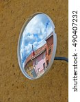 Small photo of Convex mirror in rural village on adobe wall