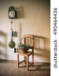 Small photo of an old pendulum clock and a basket of dried flowers on a chair. Allegory of time. vintage processing