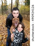 Small photo of Couple in love and American Pit Bull Terrier in the autumn park