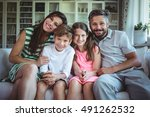 happy family sitting on sofa at ... | Shutterstock . vector #491262532